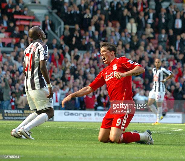 Fernando Torres of Liverpool celebrates his goal as Marco Fortune of West Bromwich Albion looks dejected during the Barclays Premier League match...