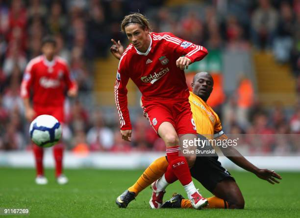 Fernando Torres of Liverpool is tackled by George Boateng of Hull City during the Barclays Premier League match between Liverpool and Hull City at...