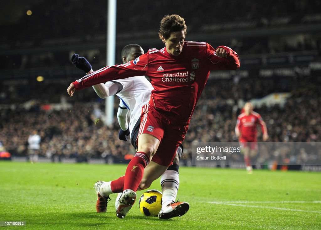 Fernando Torres of Liverpool is tackled by Sebastien Bassong of Tottenham Hotspur during the Barclays Premier League match between Tottenham Hotspur...