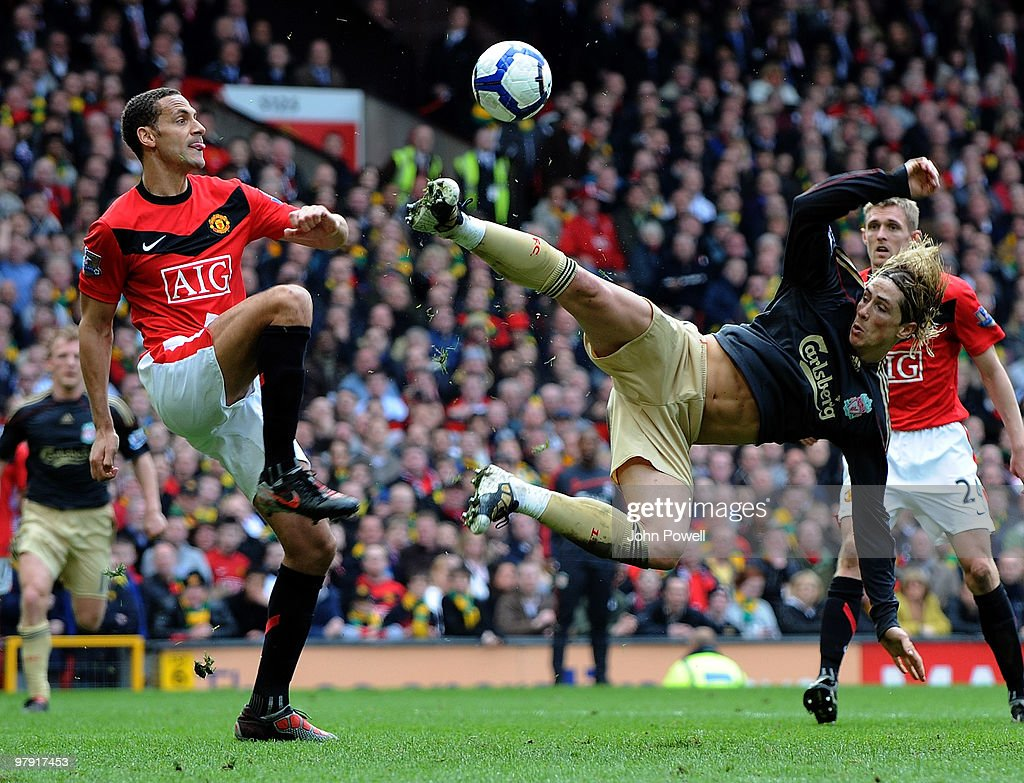 Fernando Torres of Liverpool scissor kicks the ball away from Rio Ferdinand of Manchester United during the Barclays Premier League match between Manchester United and Liverpool at Old Trafford on March 21, 2010 in Manchester, England.