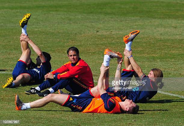 Fernando Torres of Spain stretches his leg amid his teammates Sergio Ramos Carlos Marchena and one of the teams trainers Javier Minano at the end of...