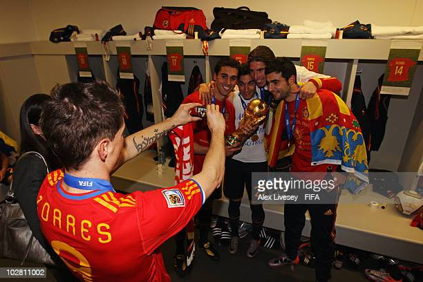 Fernando Torres of Spain takes a photo of Alvaro Arbeloa Jesus Navas Sergio Ramos and Raul Albiol in the Spanish dressing room after they won the...