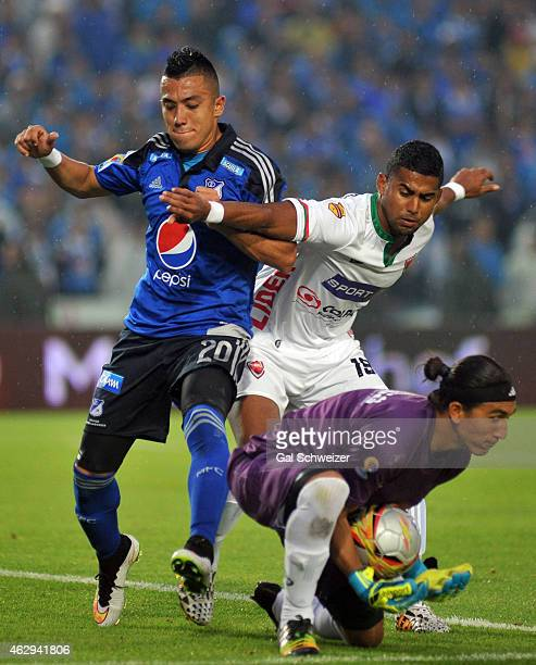 Fernando Uribe of Millonarios vies for the ball with goalkeeper Juan Castillo and player Carlos Henao of Patriotasduring a match between Millonarios...