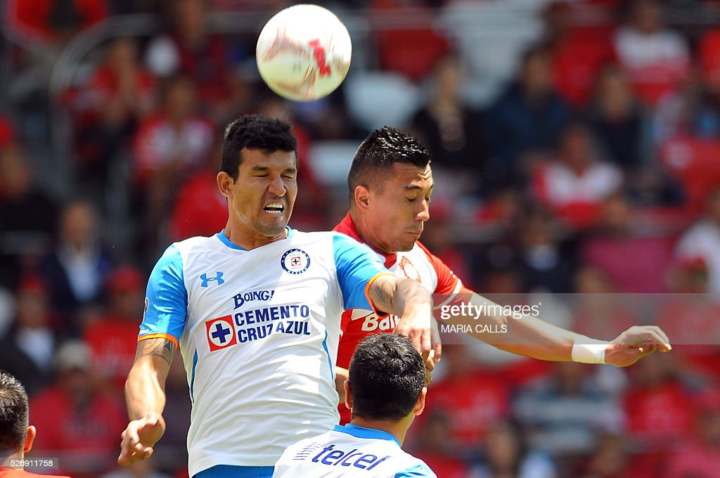 Fernando Uribe (R) of Toluca jumps for the ball with Francisco Rodriguez (L) of Cruz Azul during their Mexican Clausura 2016 football tournament match at Nemesio Diez stadium on May 1, 2016, in Toluca, Mexico. / AFP / MARIA