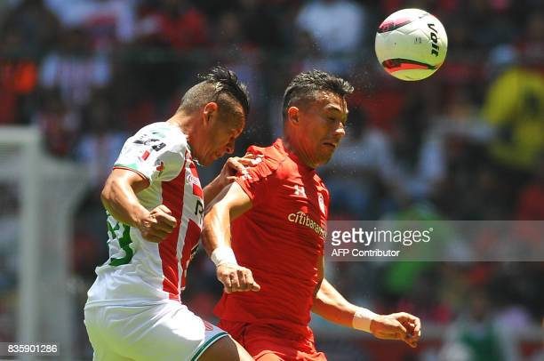 Fernando Uribe of Toluca jumps for the ball with Mario de Luna of Necaxa during their Mexican Apertura football tournament match at the Nemesio Diez...