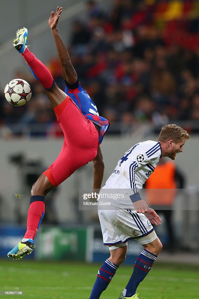 Fernando Varela (L) of Steaua Bucuresti is airborne alongside Andre Schurrle (R) of Chelsea during the UEFA Champions League Group E Match between FC Steaua Bucuresti and Chelsea at the National Arena Stadium on October 1, 2013 in Bucharest, Romania.