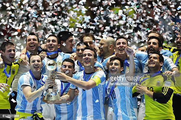 Fernando Wilhelm of Argentina lifts the winners trophy during the FIFA Futsal World Cup Final match between Russia and Argentina at the Coliseo el...