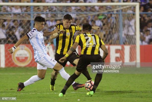 Fernando Zampedri of Argentina's Atletico Tucuman vies for the ball with Cristian Rodriguez and Ramon Arias of Uruguay's Penarol during their Copa...