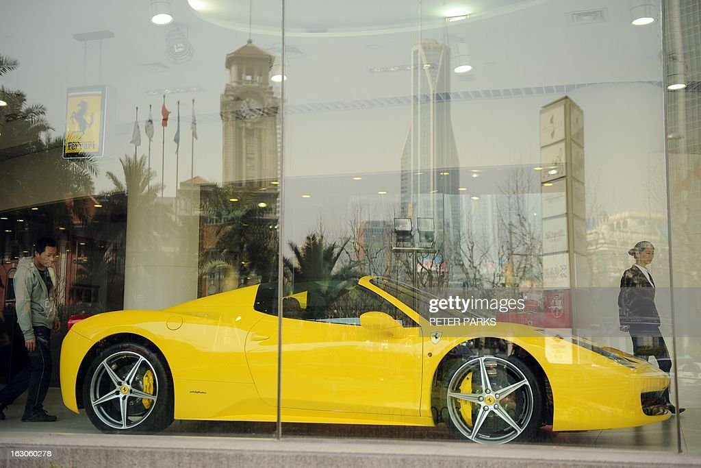 A Ferrari 458 Spider sits in a showroom in Shanghai on March 4, 2013. China will overtake the United States as the world's biggest luxury car market as early as 2016, as rising incomes and desire for status boost premium auto brands, a consultancy said. AFP PHOTO/Peter PARKS