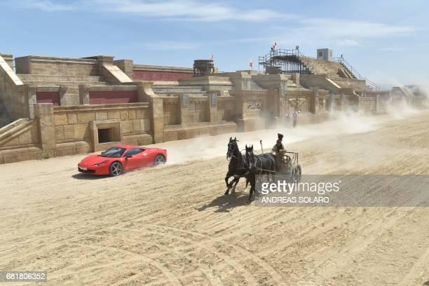 TOPSHOT Ferrari driver Fabio Barone and his Ferrari 458 Italia competes against a Roman chariot drawn by two horses on 'Ben Hur' movie set at...