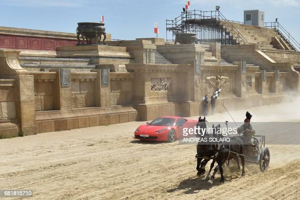 Ferrari driver Fabio Barone and his Ferrari 458 Italia competes against a Roman chariot drawn by two horses on 'Ben Hur' movie set at Cinecitta World...