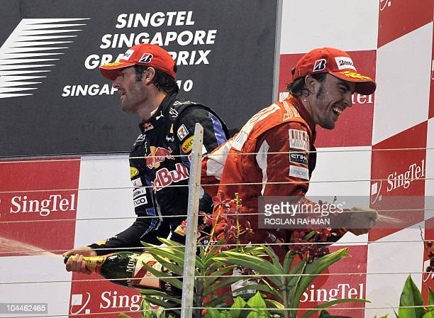 Ferrari driver Fernando Alonso of Spain and Red BullRenault driver Mark Webber of Australia spray champagne from the podium after the finish of...