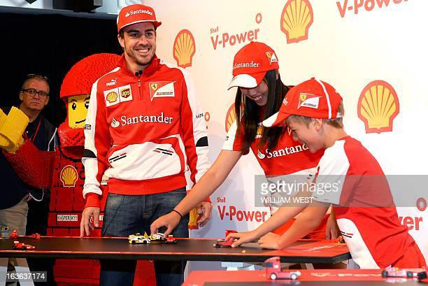 Ferrari driver Fernando Alonso of Spain plays with Lego cars with local children during a promotional event in Melbourne on March 14 ahead of the...