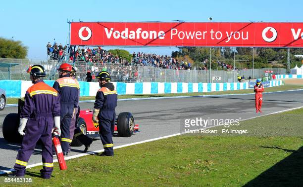 Ferrari driver Fernando Alonso stands away from his car after it stopped on a practice lap during the 2014 Formula One Testing at the Circuito de...