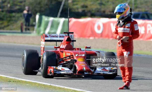 Ferrari driver Fernando Alonso stands next to his car after it stopped on a practice lap during the 2014 Formula One Testing at the Circuito de Jerez...