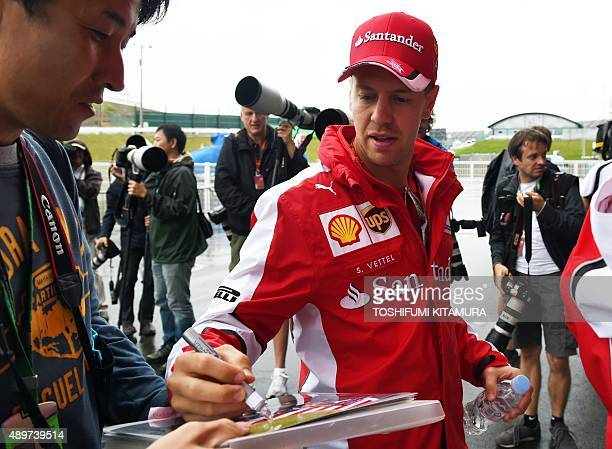 Ferrari driver Sebastian Vettel of Germany signs his autograph for a fan in the paddock area during preparations for the Formula One Japanese Grand...