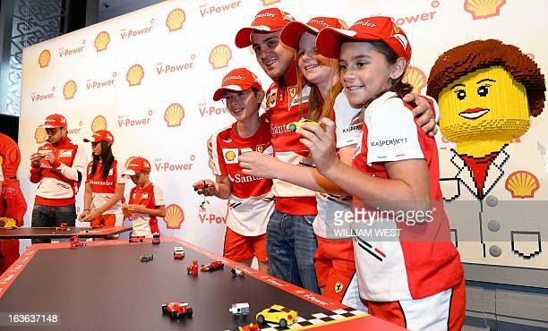 Ferrari drivers Felipe Massa of Brazil and Fernando Alonso of Spain play with Lego cars with local children during a promotional event in Melbourne...