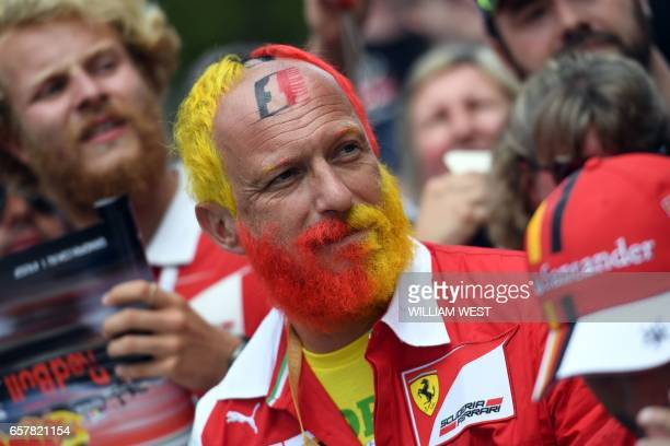 A Ferrari fan waits for the drivers to arrive before the Formula One Australian Grand Prix in Melbourne on March 26 2017 / AFP PHOTO / William WEST /...