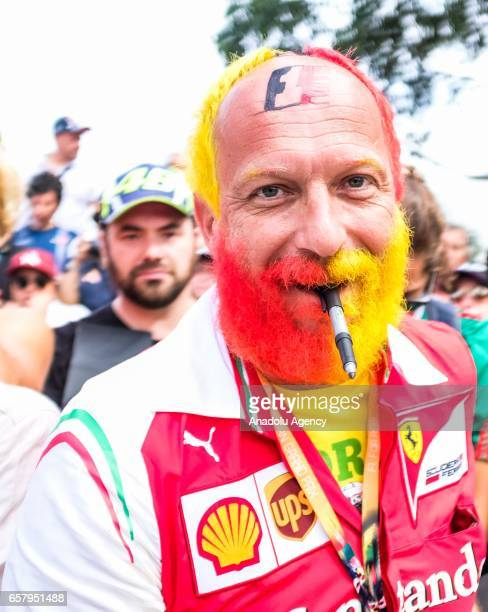 Ferrari fan with red and yellow dyed hair and beard with a pen in his mouth waits to get an autograph during the 2017 Rolex Australian Formula 1...