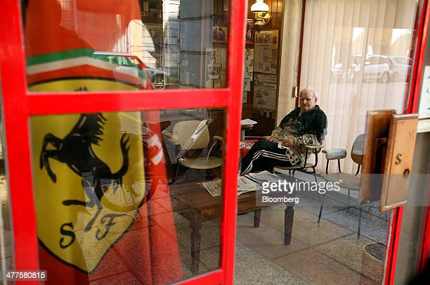 A Ferrari SpA logo sits on a flag inside the window of a barber's shop in Modena Italy on Friday March 7 2014 Banca Popolare dell'Emilia Romagna SC...