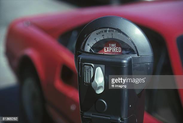 A Ferrari sports car parked by an empty parking meter circa 1985