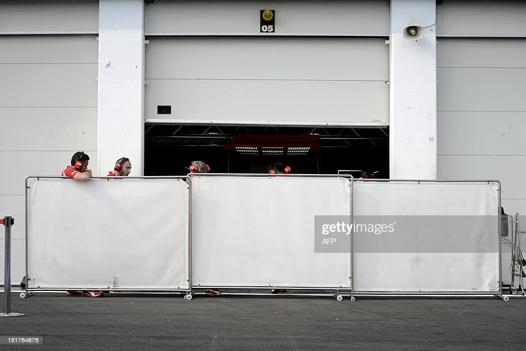 Ferrari team members work hidden behind whites panels in the pits of the Nevers Magny-Cours circuit on September 11, 2012 in Magny-Cours during a Formula One young pilots essays session. The Magny-Cours circuit previously hosted the French Grand Prix from 1991 until 2008 when the country's Motorsports Federation (FFSA) withdrew funding for the event. Magny-Cours might return to the Formula One calendar in 2013 or 2014.