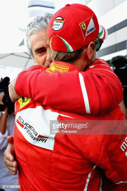 Ferrari Team Principal Maurizio Arrivabene congratulates pole sitter Sebastian Vettel of Germany and Ferrari in the Paddock during qualifying for the...