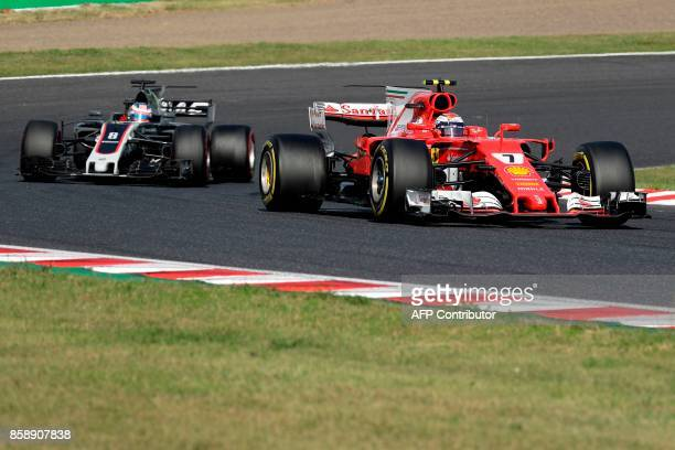 Ferrari's Finland driver Kimi Raikkonen leads Haas F1's French driver Romain Grosjean during the Formula One Japanese Grand Prix at Suzuka on October...