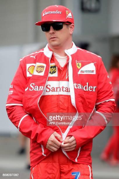 Ferrari's Finland driver Kimi Raikkonen walks in the paddock after the first practice round of the Formula One Japanese Grand Prix at Suzuka on...
