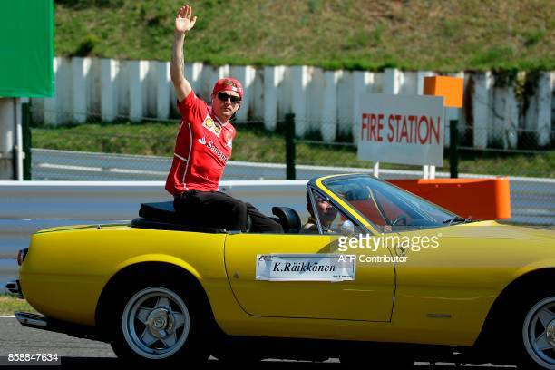 Ferrari's Finland driver Kimi Raikkonen waves to fans during the drivers' parade ahead of the Formula One Japanese Grand Prix at Suzuka on October 8...