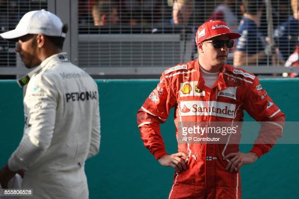 Ferrari's Finnish driver Kimi Raikkonen and Mercedes' British driver Lewis Hamilton look on following the qualifying session of the Formula One...