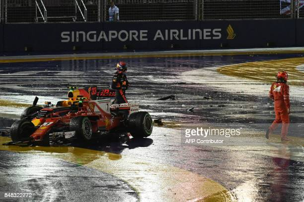Ferrari's Finnish driver Kimi Raikkonen and Red Bull's Dutch driver Max Verstappen walk away from their vehicles after a crash during the Formula One...