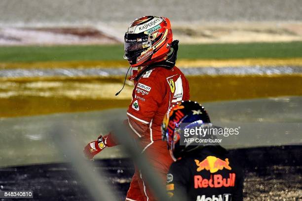 Ferrari's Finnish driver Kimi Raikkonen and Red Bull's Dutch driver Max Verstappen walk back to the pit after crashing during the Formula One...