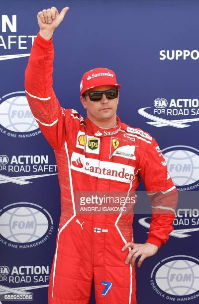 Ferrari's Finnish driver Kimi Raikkonen celebrates after winning the pole position during the qualifying session at the Monaco street circuit on May...