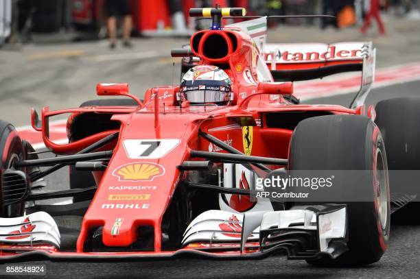 Ferrari's Finnish driver Kimi Raikkonen drives in the pit lane during the qualifying session of the Formula One Japanese Grand Prix at Suzuka on...