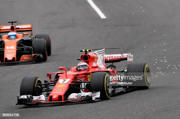 Ferrari's Finnish driver Kimi Raikkonen drives round the corner ahead of McLaren's Spanish driver Fernando Alonso during the qualifying practice of...