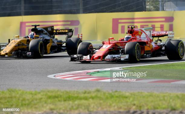 Ferrari's Finnish driver Kimi Raikkonen overtakes Renault's German driver Nico Hulkenberg during the Formula One Japanese Grand Prix at Suzuka on...