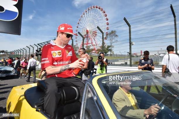 Ferrari's Finnish driver Kimi Raikkonen rides a vintage car during the drivers' parade before the start of Formula One Japanese Grand Prix at Suzuka...