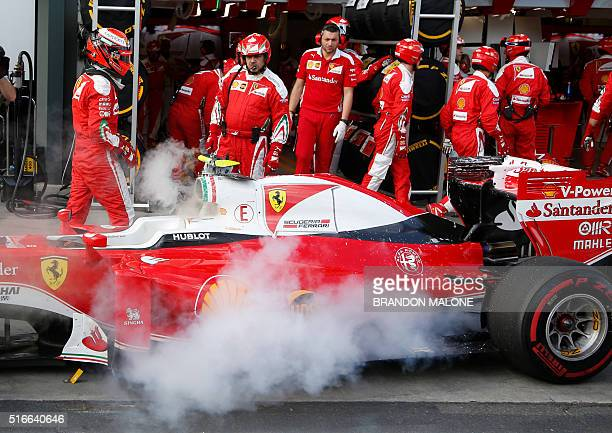 Ferrari's Finnish driver Kimi Raikkonen walks away from his car after it caught fire in the pit lane during the Formula One Australian Grand Prix in...