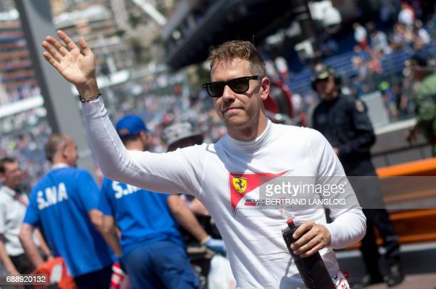 Ferrari's German driver Sebastian Vettel acknowledges the audience after winning the third practice session at the Monaco street circuit on May 27...