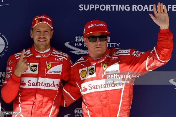Ferrari's German driver Sebastian Vettel and Ferrari's Finnish driver Kimi Raikkonen pose after the qualifying at the Hungaroring racing circuit in...