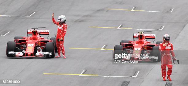 Ferrari's German driver Sebastian Vettel and Finnish driver Kimi Raikkonen leave their cars after the Brazilian Formula One Grand Prix Q3 qualifying...