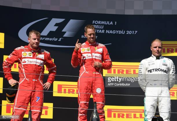 Ferrari's German driver Sebastian Vettel celebrates after winning the Formula One Hungarian Grand Prix at the Hungaroring racing circuit in Budapest...