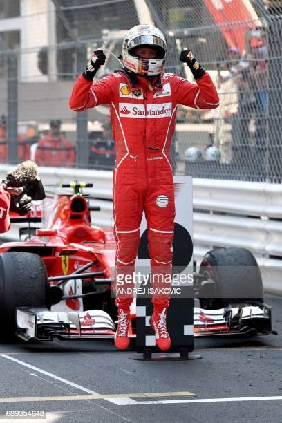 Ferrari's German driver Sebastian Vettel celebrates as he leaves his car after winning the Monaco Formula 1 Grand Prix at the Monaco street circuit...