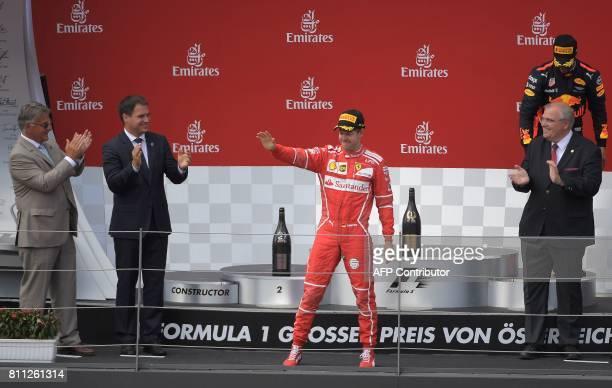 Ferrari's German driver Sebastian Vettel celebrates his second place on the podium the Formula One Austria Grand Prix at the Red Bull Ring in...