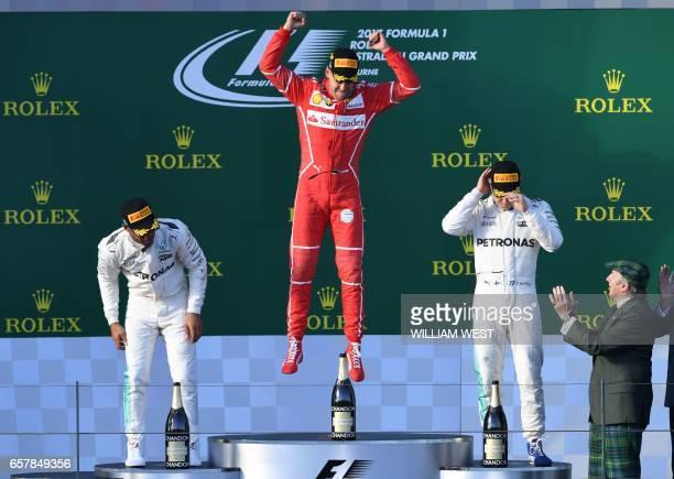 TOPSHOT Ferrari's German driver Sebastian Vettel celebrates on the podium beside secondplaved Mercedes' British driver Lewis Hamilton and thirdplaced...