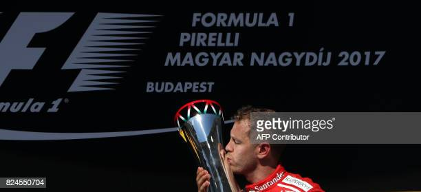 TOPSHOT Ferrari's German driver Sebastian Vettel celebrates on the podium with his trophy at the Hungaroring racing circuit in Budapest on July 30...