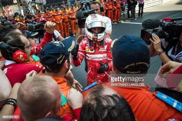 Ferrari's German driver Sebastian Vettel celebrates with his team members as he leaves his car after winning the Monaco Formula 1 Grand Prix at the...