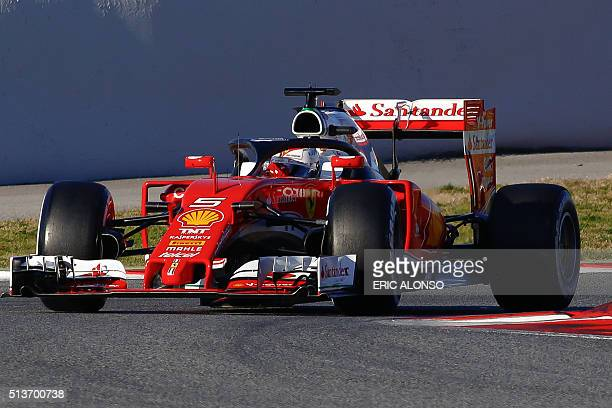 Ferrari's German driver Sebastian Vettel drives a car sporting a prototype protective cage over the cockpit dubbed Halo at the Circuit de Catalunya...