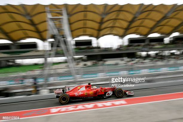 Ferrari's German driver Sebastian Vettel drives in pit lane during the second practice session of the Formula One Malaysia Grand Prix in Sepang on...
